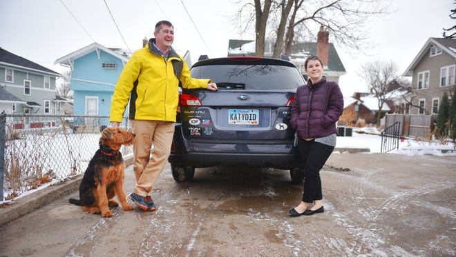"""Matt and Kate Parker and their dog June show off their vanity license plates Tuesday, Jan. 30, at their home in Sioux Falls. Kate's license plate says """"KATYDID"""" and Matt's says """"JHAWK."""""""