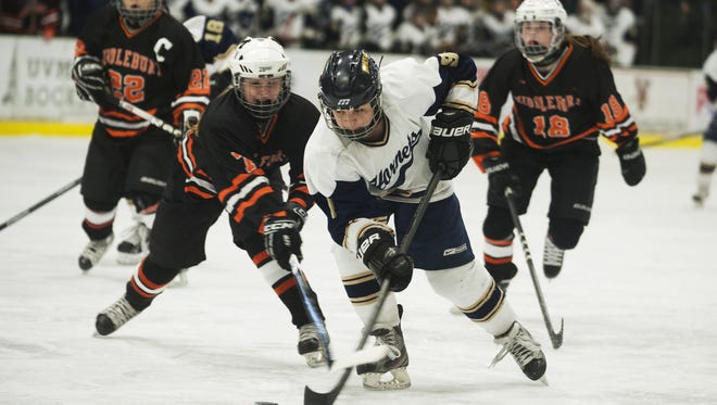 Essex's Kathleen Young (9) skates past Middlebury's Julia Carone (7) during the division I high school girls hockey championship between the Middlebury Tigers and the Essex Hornets at Gutterson Fieldhouse.