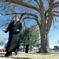 Dolores Archuleta, Las Esperanzas, Inc. member, left, steps away to get a better look at the location where a memorial for Miguel Silva will be placed. The group has planned to place plaque and a large-scale bowtie around the trunk of the tree in  memory of the former city councilor. Pictured in the background holding the tape measure is Sandy and Scott Murray.