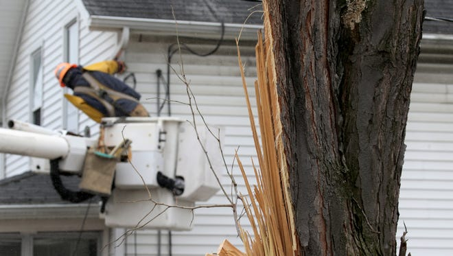 Jeremy Kearns with Northline Utilities restores electric lines to homes in Irondequoit after the windstorm.