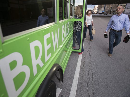 Customers, including Tim Quick (right), and Sarah Sloan, both of Fishers, board the Indy Brew Bus, Indianapolis, Friday, October 3, 2014.