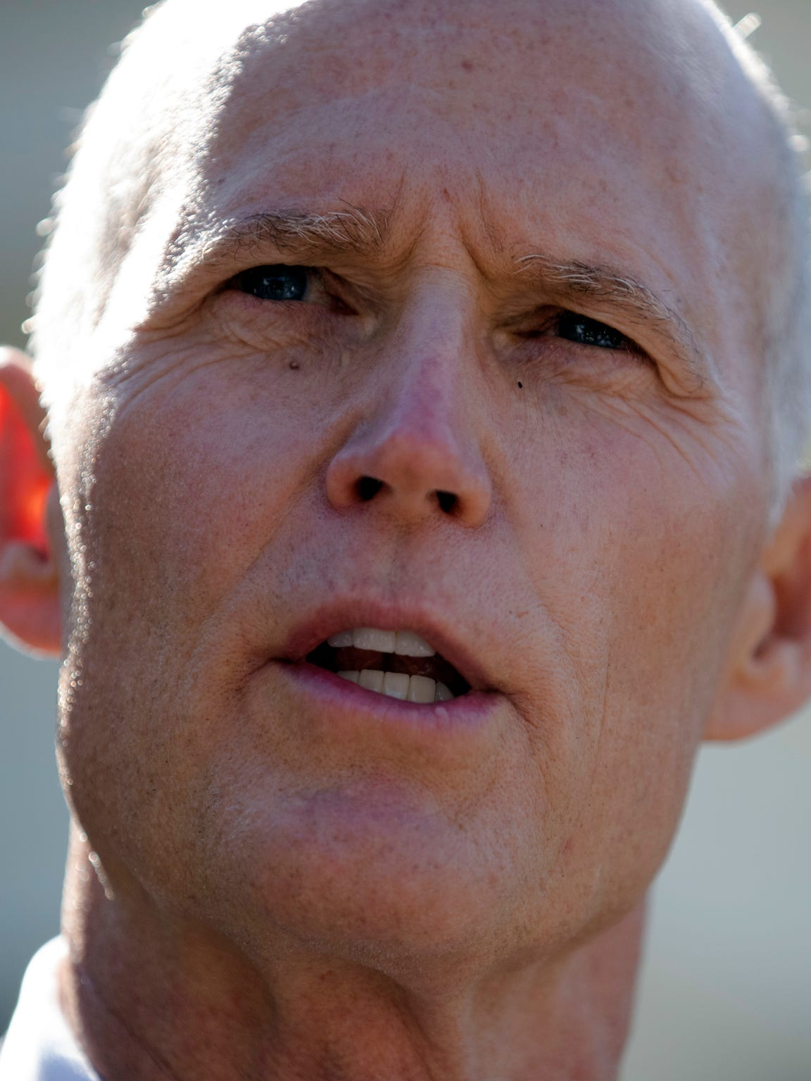 Gov. Rick Scott talks to the media outside the West