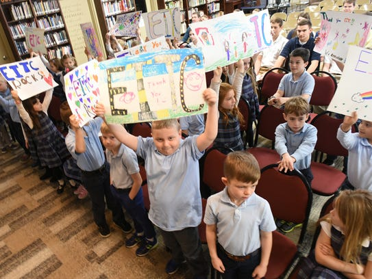 First-grade students raise signs they made during an