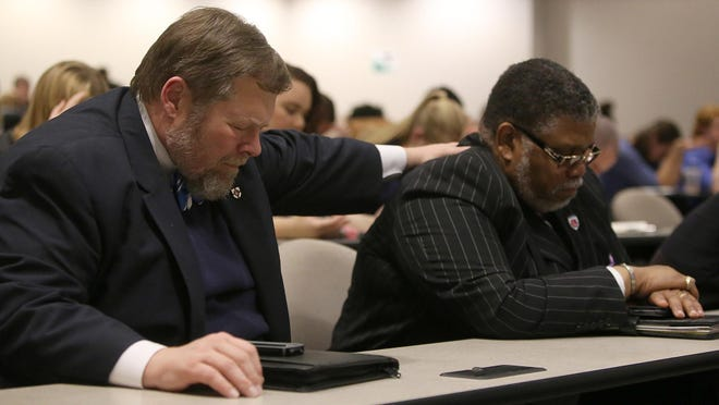 Union University Provost and Vice President for Academic Affairs C. Ben Mitchell, left, and Lane College Assistant Professor of Religion Daryll Coleman pray together at the end of the Black Education Matters discussion Tuesday at Union University's Harvey Hall.