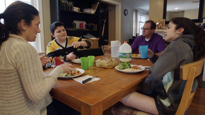 """This photo provided by Kikim Media shows the Scavotto family sitting down to dinner, in a scene from the documentary film, """"In Defense of Food."""" Anthony, second left, was referred to a program for overweight kids at Boston Children's Hospital after gaining 30 pounds in one year.The film is based on Michael Pollan's book, """"In Defense of Food,"""" and premieres on PBS Wednesday."""