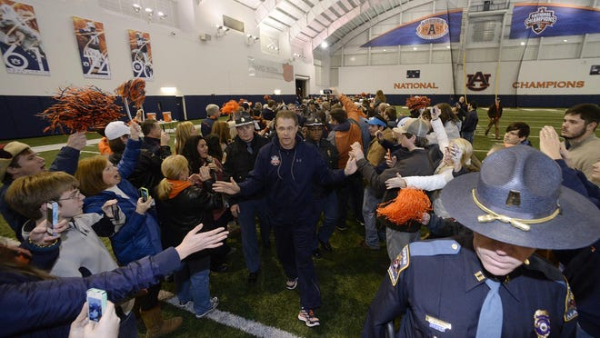 Auburn coach Gus Malzahn leads his team through the crowd at the indoor practice facility after the team's return from the post-season playoff game in Pasadena on Jan. 7, 2014.