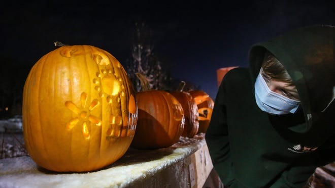 "Oliver Brown, of Holliston, inspects a pumpkin during the first  ""Jack-O'-Lantern Stroll"" along West Main Street in Northborough Friday night."