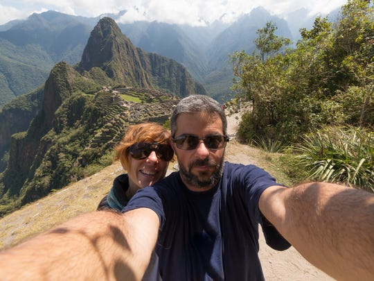 Tourists take a selfie on the terraces above Machu