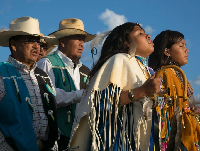 Kaila Perry (in white) dances with her friend, Meleah Amos, in front of the Burnette Singers led by Medicine Man Harris Burnette during the Sunrise Ceremony near Cedar Creek on the Fort Apache Reservation.