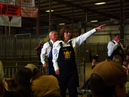 Wichita County District Attorney Maureen Shelton serves as an auction spotter during the recent Wichita County Junior Livestock show, where friends of the late Heath Hodges bid on a toy John Deer tractor.
