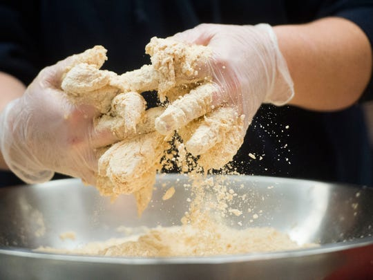 Employee Sarah Kaneifs prepares Krispy Krunchy Chicken, which was recently called the country's best fast-food fried chicken, at the Keith Avenue Market owned by Jimmy Murfiq in Knoxville Tuesday, Jan. 30, 2018.