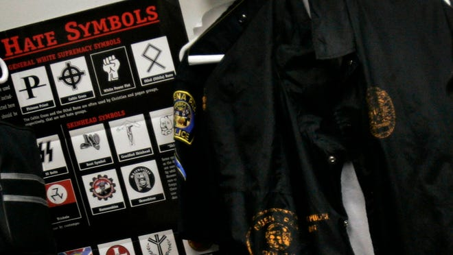 A poster displaying hate symbols hang in the gang unit office at the police station in Buena Park, Calif.
