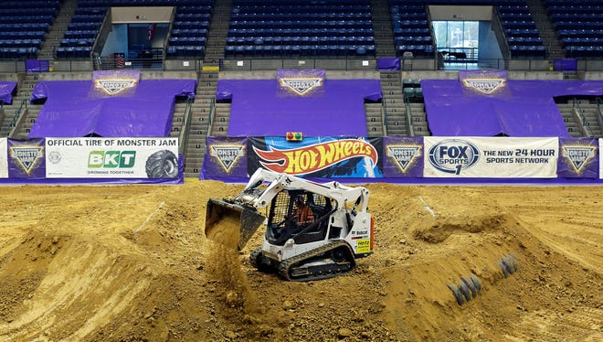 A crew member builds a monster truck ramp inside the Mississippi Coliseum Thursday. Monster Jam monster truck shows will begin Friday, Nov. 11 at 6:30 p.m. and continue through Sunday.