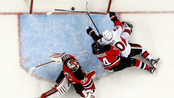 A shot by Ottawa Senators defenseman Erik Karlsson, not pictured, of Sweden, enters the net of New Jersey Devils goalie Cory Schneider (35) for a goal during the third period of an NHL hockey game, Thursday, Feb. 16, 2017, in Newark, N.J. The Senators won 3-0. Also seen are Senators' Tom Pyatt (10) and Devils' Adam Henrique (14) on the play. (AP Photo/Julio Cortez)