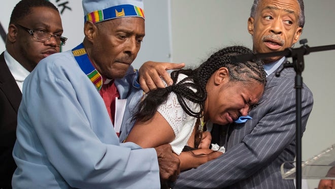 Esaw Garner, center, wife of Eric Garner, breaks down in the arms of the Revs. Herbert Daughtry and Al Sharpton, right, during a rally Saturday in New York for Eric Garner. Garner, 43, died Thursday in police custody.