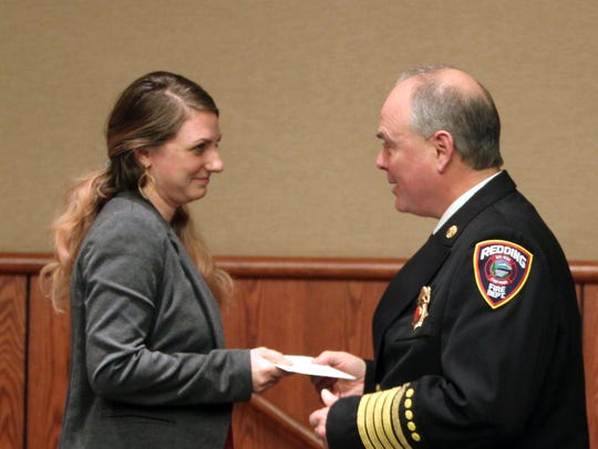 Ashley Crockett, left, presents Redding Fire Chief