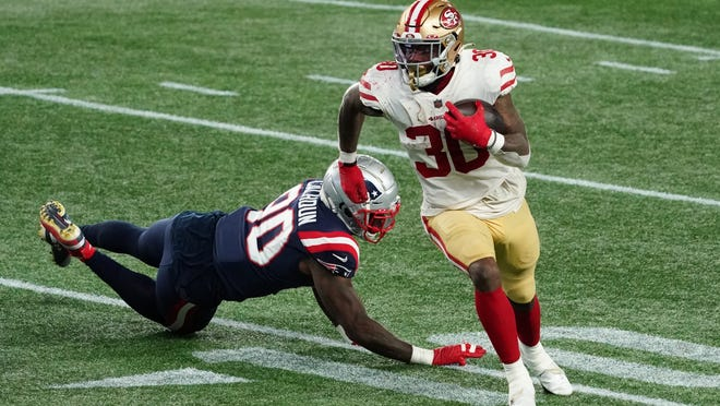 49ers running back Jeff Wilson (right) runs the ball for a touchdown past Patriots linebacker Shilique Calhoun in the second half of San Francisco's 33-6 victory at Gillette Stadium on Sunday.