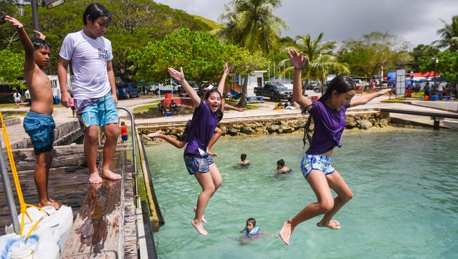 Cousins Jilina Ford, right, and Sarajane Fairfield, are joined by other kids as they take a cooling dip in after leaping from the Malesso Pier in this Nov. 4, 2017, file photo. The annual Malesso Fiestan Tasi is set for this weekend