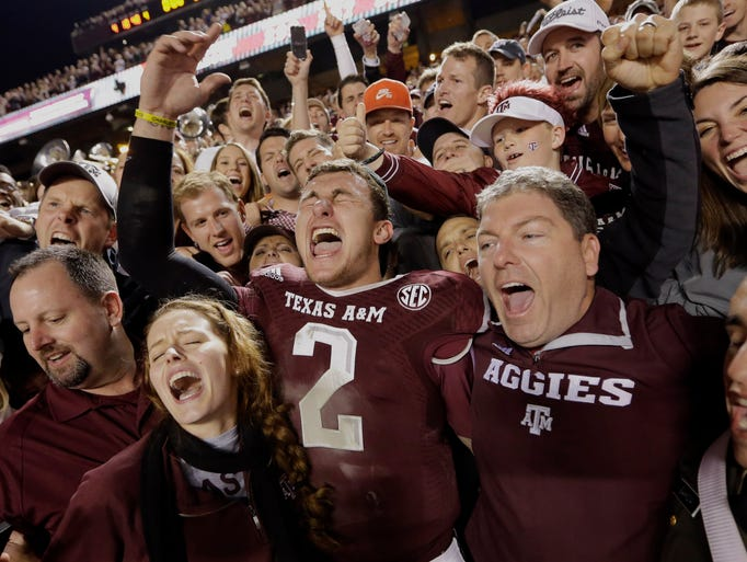 Texas A&M quarterback Johnny Manziel  celebrates with fans after defeating Mississippi State.