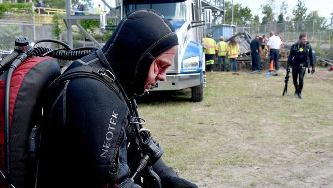 """Former Monroe Police Cpl. Kent Klemz, a member of the Monroe County Sheriff's diving team, said it was """"black diving; you cannot see anything,"""" after the second dive Wednesday afternoon."""