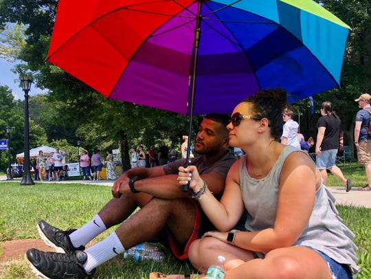 Two attendees sit under an umbrella and listen to a