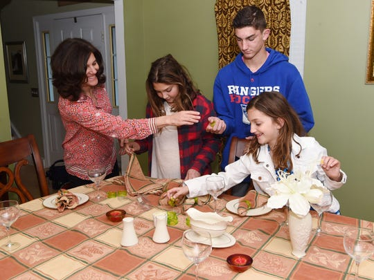 Lucille Grippo, 45, left, sets the dining room table with her children for Thanksgiving. From left to right: Mia, 11; Nicholas, 14; and Audrey, 8. In June, Lucille lost her pulse for 35 minutes. She has recovered with minimal repercussions. Not pictured is husband Patrick Grippo, 43.