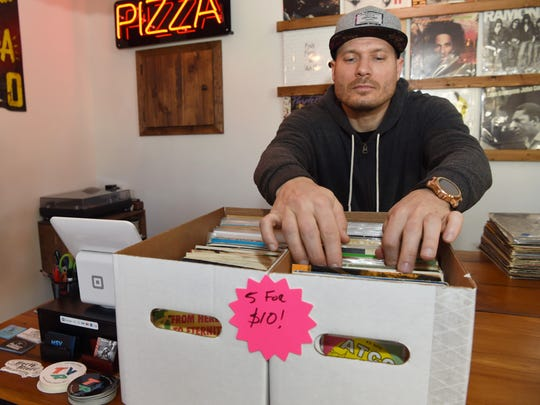 John Kihlmire, owner of the The Vinyl Room in Wappingers Falls, goes through some merchandise on Black Friday.