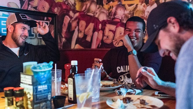 Taylor Hillson (left to right), Felix Baez and Shane Weedman share a laugh as they dine with Allen Weinbach (not pictured) to celebrate Weedman's 25th birthday on one of their off days at Applebees in Evansville, Ind., on Monday, Aug. 7, 2017. Weinbach has been hosting Otters players at his home since 2000 and provided three rooms for the players to stay in throughout the 2017 season.