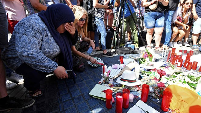 People gather next to flowers, candles and other items set up on the Las Ramblas boulevard in Barcelona as they pay tribute to the victims of the Barcelona attack.