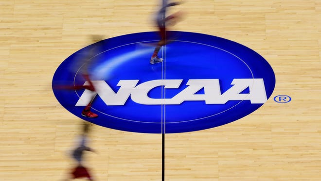 Mar 27, 2014; Indianapolis, IN, USA; Louisville Cardinals players run across the logo at center court during practice for the midwest regional of the 2014 NCAA Tournament at Lucas Oil Stadium. Mandatory Credit: Bob Donnan-USA TODAY Sports