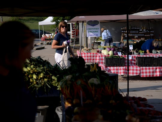 Traci Dudley browses produce on Wednesday, Aug. 3, 2016 at the Meridian Township Farmers Market in Okemos.
