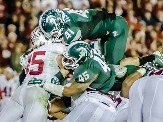 Kyler Elsworth (41) of MSU and teammate Darien Harris (45) stop Ryan Hewitt of Stanford on a 4th and 1 with 1:45 remaining in the 4th quarter of the 2014 Rose Bowl.