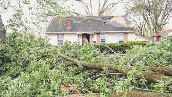 People look at damage that affected hundreds of homes Saturday in Orrick. A confirmed tornado that was part of a supercell storm hit the town of Orrick on Saturday evening.