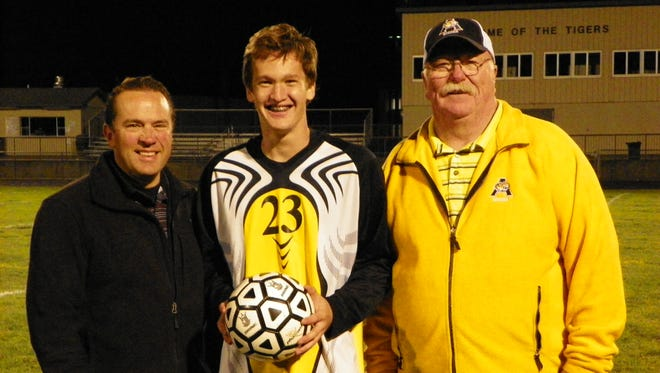 Lincoln Alcona goalie Conner McCoy, center, poses with head coach Tim Munro, right, and assistant coach Tim Steiner after breaking the nation's career saves record for boys high school soccer on Sept. 27, 2017, in Lincoln, Mich.