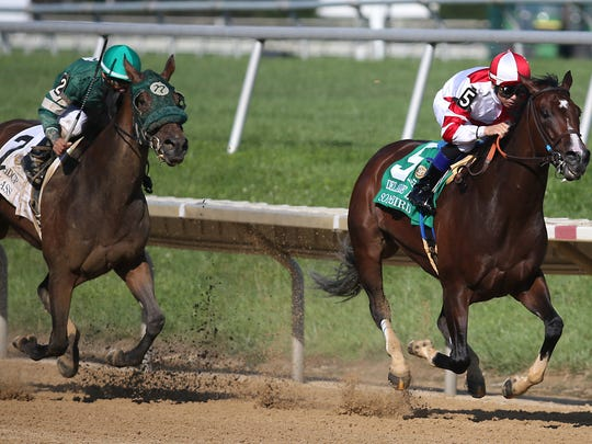 Heavy favorite Songbird (right) with Mike Smith aboard, holds off a late charge by Martini Glass and Jose C. Ferrer  to win the Delaware Handicap Saturday at Delaware Park.