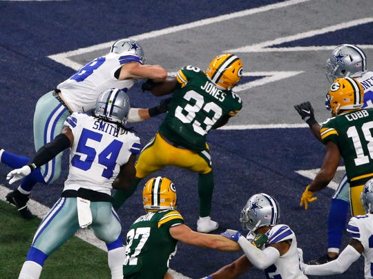 Green Bay Packers running back Aaron Jones (33) breaks into the end zone past Dallas Cowboys linebacker Jaylon Smith (54) for a touchdown in the first half of an NFL football game, Sunday, Oct. 8, 2017, in Arlington, Texas. (AP Photo/Ron Jenkins)