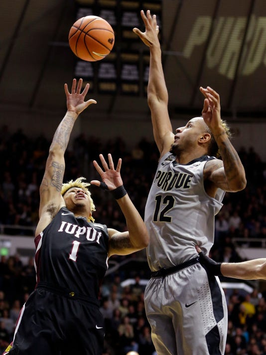 Purdue forward Vincent Edwards (12) blocks the shot of IUPUI guard T.J. Henderson (1) in the first half of an NCAA college basketball game in West Lafayette, Ind., Sunday, Dec. 10, 2017. (AP Photo/Michael Conroy)