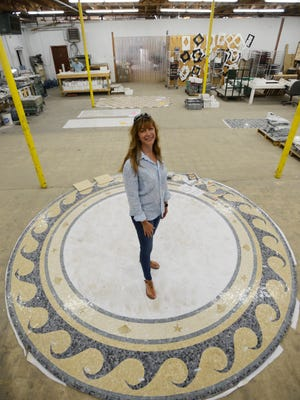 Sara Baldwin stands in the middle of a circular mosaic tile design at New Ravenna Mosaics in Exmore, Va. on Tuesday, June 5, 2014. Baldwin is the owner and founder of the company.