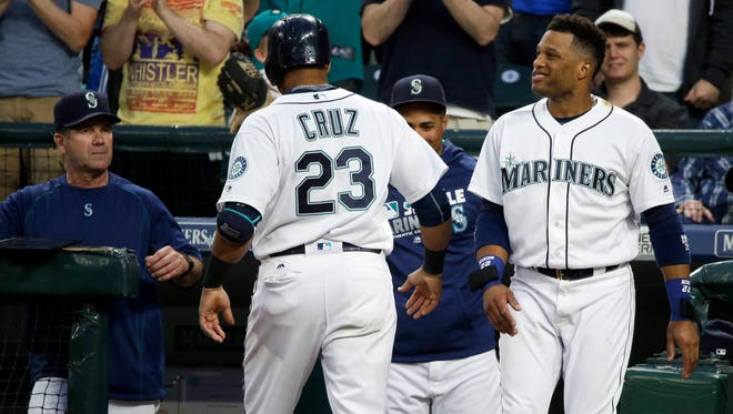 Seattle Mariners' Nelson Cruz (23) is greeted at the dugout by teammate Robinson Cano, right, and hitting coach Edgar Martinez, left, after Cruz hit a solo home run against the Cleveland Indians duiring the fifth inning of a baseball game, Tuesday, June 7, 2016, in Seattle. It was Cruz's second home run of the game. (AP Photo/Ted S. Warren)
