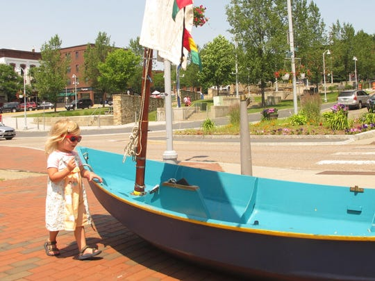 Louisa Duncan, 2, of Winooski, examines a small sailboat Saturday at the entrance to French Heritage Day festivities.