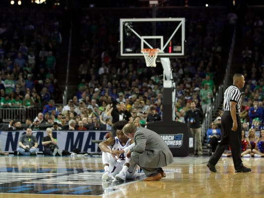 A trainer checks on Kansas guard Devonte' Graham (4) during the first half of an NCAA men's college basketball tournament second-round game against Seton Hall, Saturday, March 17, 2018, in Wichita, Kan. (AP Photo/Orlin Wagner)