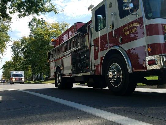 Emergency vehicles lead a procession, escorting Jon-Marc
