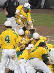 Shortstop Drew LaBounty, top, leaps on the dogpile