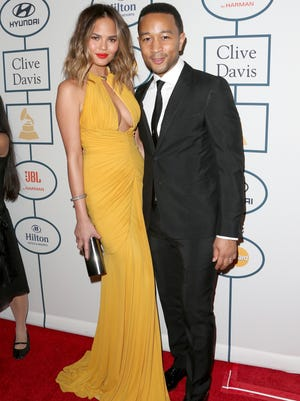 John Legend and his wife, model Chrissy Teigen, attend the the Pre-Grammy Gala and Salute to Industry Icons on Jan. 25, 2014 in Beverly Hills, Calif.