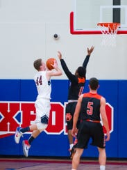 New Oxford's John Wessel (44) goes for a shot against