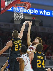 USD's Trey Burch-Manning goes for a shot over SDSU's Reed Tellinghuisen last year in Vermillion.