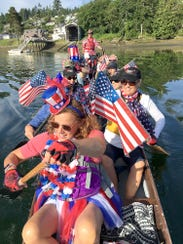 The Gig Harbor Dragons head out into the harbor festooned