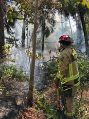 Naples firefighters put out a small fire behind the
