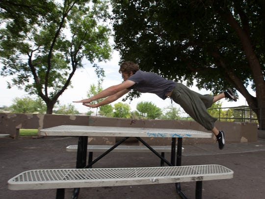 Joseph Lanning, a certified parkour instructor, utilizes a table at Young Park to demonstrate some of the moves that can be incorporated into parkour.