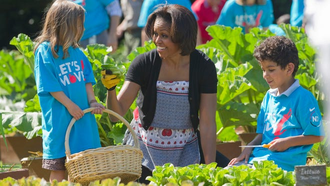 """First lady Michelle Obama tends the White House garden in Washington, with a group of children as part of the """"Let's Move!"""" campaign on June 3, 2011. A government report published online Tuesday, Feb. 25, 2014, in The Journal of the American Medical Association found that, overall, both adult and childhood obesity rates have been flat in the past decade however, the preschool obesity rate _ those children ages 2 to 5 _ decreased to 8 percent, from 14 percent a decade ago. That would represent a 43 percent drop. While Obama's """"Let's Move"""" campaign and other efforts over the past 10 years have raised awareness about childhood obesity, stumbling blocks remain for some working parents."""